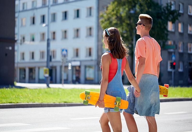 adolescente pareja con patinetas en Ciudad crosswalk