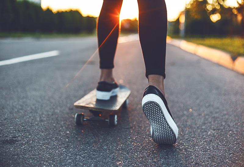 jóvenes patinador piernas montar en monopatín